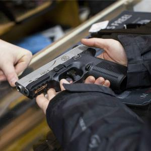 A customer inspects a handgun © Kris Tripplaar/Sipa USA/Rex Feat