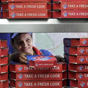 A worker at Domino's Pizza hands off a pizza for delivery © Jason Alden/Bloomberg via Getty Images