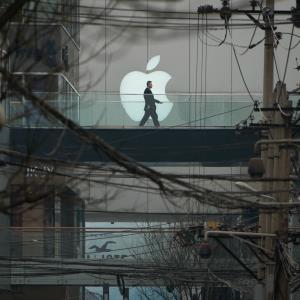 A man walks past an Apple logo displayed above a street at a shopping mall in Beijing © Ed Jones/AFP/Getty Images