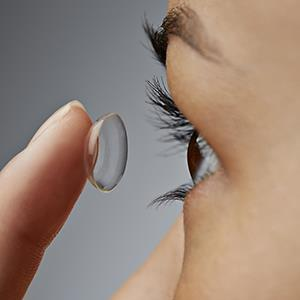 Woman putting in contact lens © Klaus Vedfelt/Getty Images