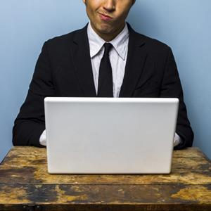 Confused businessman working on laptop © Istock/360/Getty Images