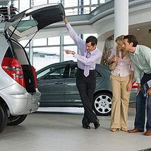 Image: Car salesman showing couple new silver hatchback in car showroom © Juice Images/Cultura/Getty Images