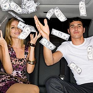 Wealthy couple celebrating in a car © Image Source/Getty Images