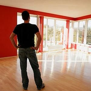 Man looking at empty living room © BilderLounge/SuperStock