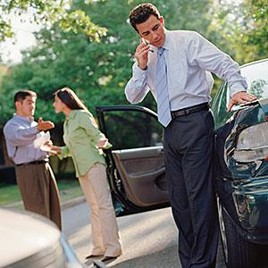 Businessman talking on his cell phone by a car accident © Stewart Cohen, Blend Images, Getty Images