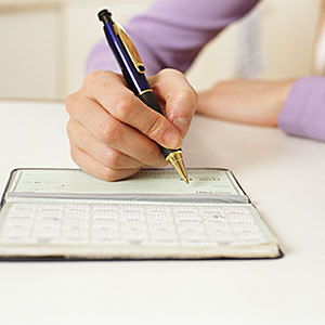 Woman writing in check book © Bruce Laurance/Digital Vision/Getty Images