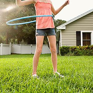 Girl hula hooping in backyard © Pauline St. Denis, Tetra images, Getty Images