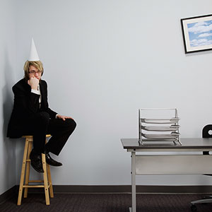 Office worker sitting in the corner, wearing dunce hat © Design Pics/Corbis