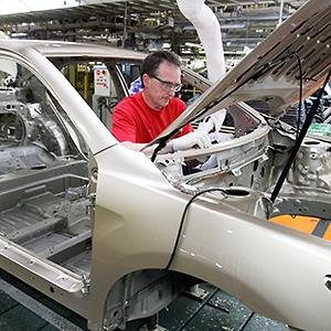 Caption: An auto worker installs parts on a Camry on the assembly line at the Toyota Motor Manufacturing plant in Georgetown, Ky.