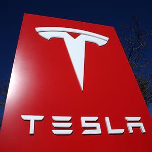 Credit: © Justin Sullivan/Getty ImagesCaption: A sign for a Tesla showroom in Palo Alto, Calif.