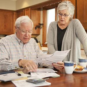 Senior couple together at the kitchen table working on home finances © Yellow Dog Productions/Getty Images