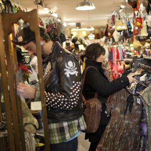 21-year-old Denise Romero looks for a blouse while shopping in a Brooklyn, N.Y. thrift store © Robert Nickelsberg/Getty Images