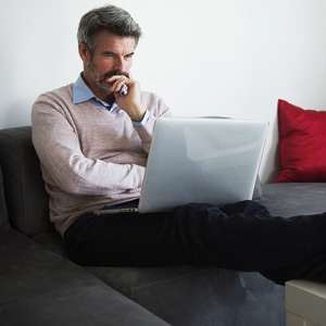 Man on couch with a laptop © Cavan Images/Getty Images
