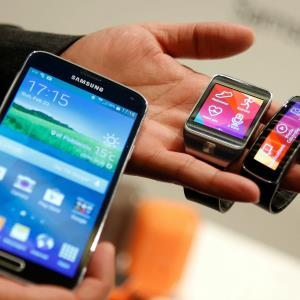 New Samsung Galaxy S5 smartphone (left), Gear 2 smartwatch (center) and Gear Fit fitness band are displayed at the Mobile World Congress in Barcelona (c) ALBERT GEA/Newscom/RTR