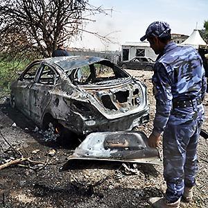 Credit: © Khalil Al-A'Nei/EPACaption: An Iraqi policeman inspects the site of a car bomb attack in Kirkuk city, northern Iraq, June 04, 2014