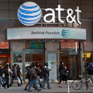 Pedestrians walk by an AT&T store in Times Square on February 21, 2013 in New York City (© Ben Hider/Getty Images)