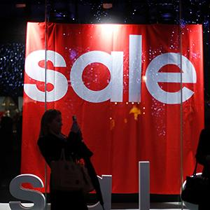 A woman in front of a sale sign (© Andrew Winning/Reuters)