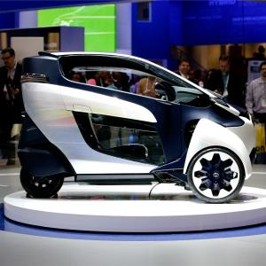 People look at the Toyota i-Road electric three-wheeler concept at the International Consumer Electronics Show (CES) on Tuesday, Jan. 7, 2014, in Las Vegas. (AP Photo/Jae C. Hong)