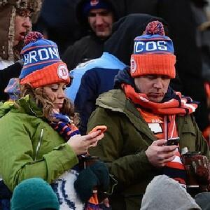 Denver Broncos fans on their cell phones at Mile High stadium. Credit: Ron Chenoy-USA TODAY Sports