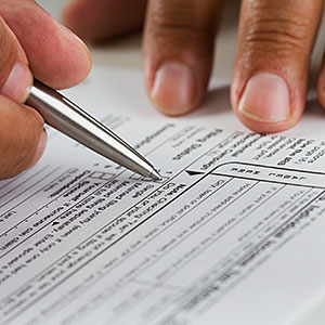 Close up of hands filling in tax form © JGI, Blend Images, Getty Images
