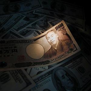 Light is cast on a Japanese 10,000 yen note placed atop U.S. dollar notes © Yuriko Nakao/Reuters