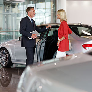 Salesman talking to woman in automobile showroom © Adam Gault/OJO Images/Getty Images