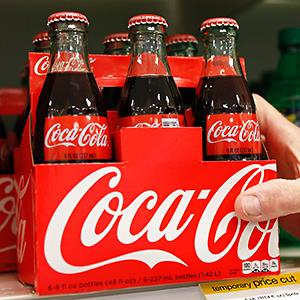 Caption: An employee arranges bottles of Coca-Cola at a store in Alexandria, Va.Credit: © Kevin Lamarque/Reuters