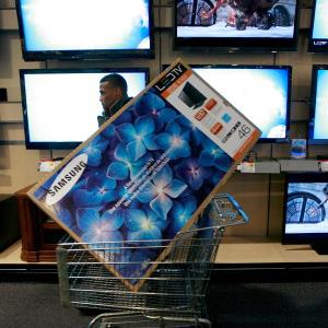 "A shopper carrying 46"" television while shopping at Best Buy © Tom Pennington/Getty Images"