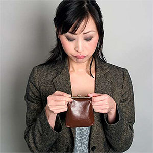 Woman looking at coin purse © Meiko Arquillos, Getty Images