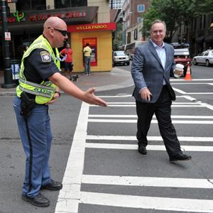 A police officer directs a pedestrian in Charlotte, NC