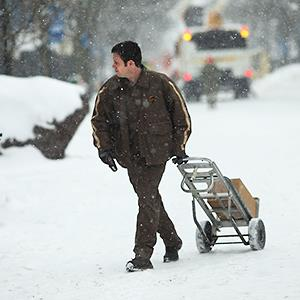 Caption: A UPS worker makes deliveries during a snow storm on February 5, 2014 in Burlington, Vermont