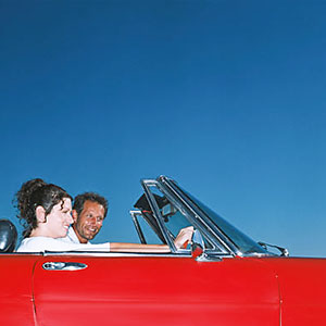 Couple driving in convertable © Image Source, SuperStock