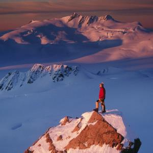 Hiker on a mountaintop in New Zealand (c) Getty Images