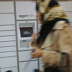 File photo of a woman walking past an Amazon locker in New York © Spencer Platt/Getty Images
