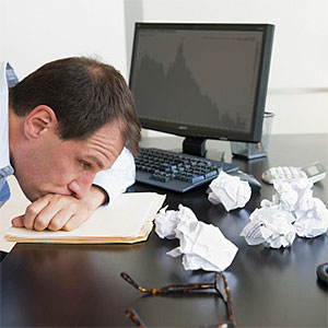 Businessman with face down on desk © Tetra Images, Tetra images, Getty Images