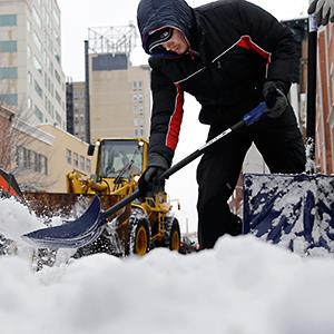 Workers clear newly-fallen snow from a street Tuesday, Feb. 18, 2014, in Trenton, N.J. © Mel Evans/AP