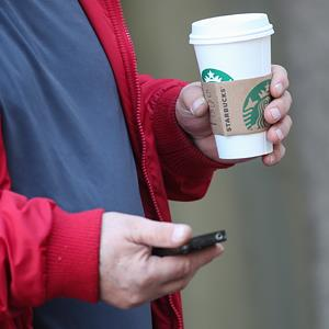 A customer exits a Starbucks Coffee with a coffee and a cellphone © Nicolaus Czarnecki/ZUMAPRESS/Corbis