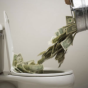 Money into toilet © RubberBall/SuperStock