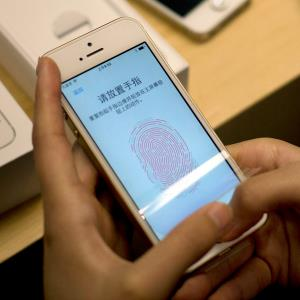 A customer configuring the fingerprint scanner technology built into iPhone 5S at an Apple store in Beijing. (AP Photo/Andy Wong)