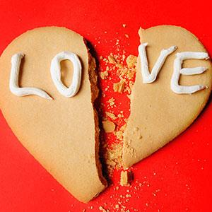 Heart-shaped 'love' cookie broken in half © Ingram Publishing/SuperStock